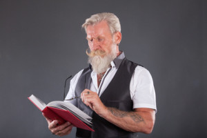 Cool senior man is reading a book on a table . The beard man is wearing a waistcoat and glasses.